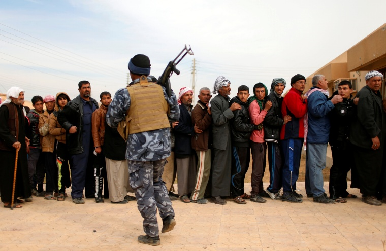 Iraqis wait outside a distribution point run by United Nations agencies at Zahra district