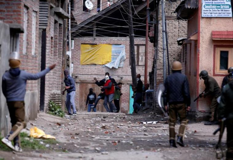 Kashmiri demonstrators throw stones towards Indian policemen during a protest against by-polls in Srinagar